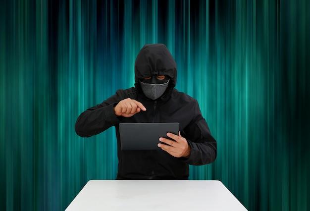 Hacker incappucciati anonimi che hackerano i dati del tablet su uno sfondo di strisce verticali luminose e scure