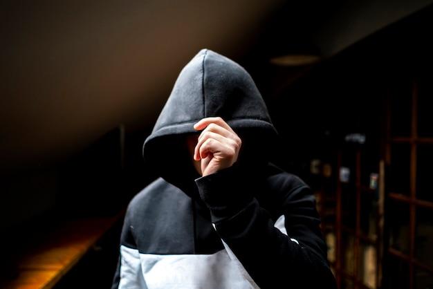 Uomo anonimo nel cappuccio scuro in piedi nella misteriosa posa