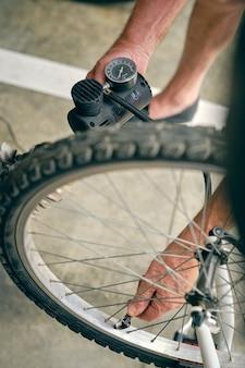 Uomo anonimo che pompa la ruota della bicicletta