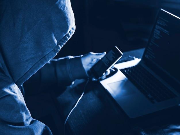 Persona anonima nel cofano seduta davanti al computer che lavora con un laptop e un telefono cellulare