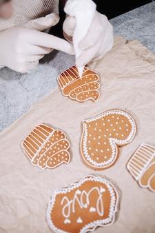 Donna anonima che decora alcuni biscotti di pan di zenzero fatti in casa in cucina