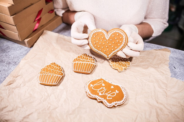 Donna anonima che decora alcuni biscotti fatti in casa del pan di zenzero del cuore alla cucina