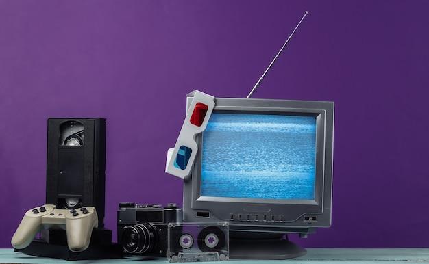Antenna ricevitore tv retrò vecchio stile, occhiali stereo anaglifi, audio e videocassetta, gamepad, fotocamera su viola.