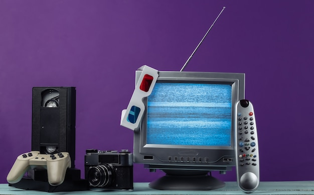 Antenna ricevitore tv retrò vecchio stile, occhiali stereo anaglifi, audio e videocassetta, gamepad, fotocamera, telecomando su viola.
