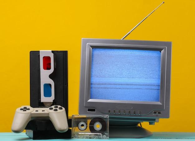 Antenna ricevitore tv retrò vecchio stile, occhiali stereo anaglifi, audio e videocassetta, gamepad su giallo.