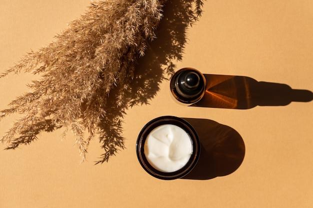 Siero viso antietà al collagene in flacone di vetro scuro e crema per il viso su fondo beige con copia spazio. concetto di bellezza cosmetica biologica naturale.