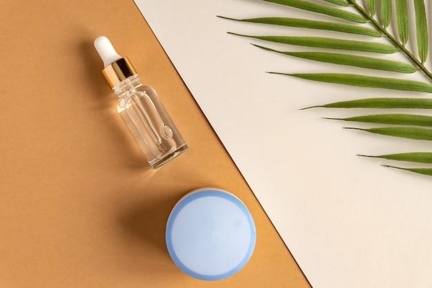 Siero viso antietà al collagene in flacone di vetro trasparente con pipetta d'oro e crema per il viso