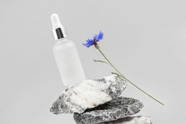 Collagene antietà, siero viso in bottiglia di vetro trasparente con pipetta su un mucchio di pietre e fiore di fiordaliso blu su sfondo grigio.