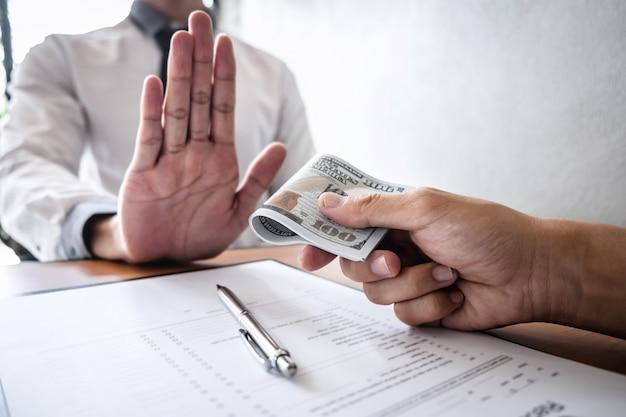 Concetto anti corruzione e corruzione, uomo d'affari che rifiuta e non riceve banconote in denaro nell'involgere l'offerta da parte degli uomini d'affari di accettare un contratto di accordo di investimento