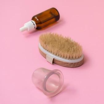 Accessori anticellulite pennello a secco, olio, ventosa in silicone sottovuoto su sfondo rosa pastello