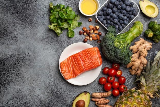Concetto di dieta antinfiammatoria. set di alimenti che aiutano a ridurre l'infiammazione - ingredienti a base di piante, frutta fresca, verdure verdi. prodotti dietetici sani, vista dall'alto, spazio di copia di sfondo in pietra stone