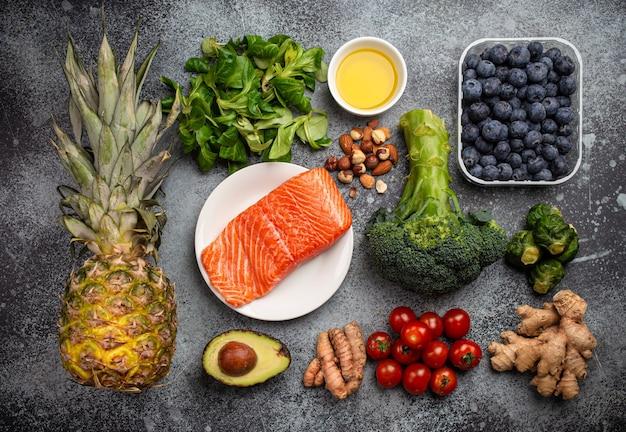 Concetto di dieta antinfiammatoria. set di alimenti che aiutano a ridurre l'infiammazione - ingredienti a base di piante, frutta fresca, verdure verdi. prodotti dietetici sani, vista dall'alto, sfondo di pietra