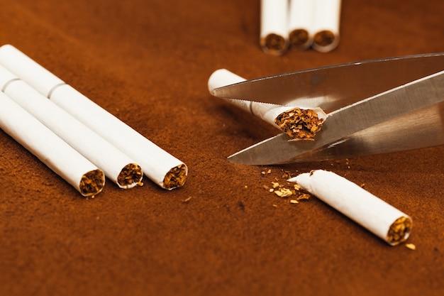 Concetto antifumo, forbici che tagliano la sigaretta.