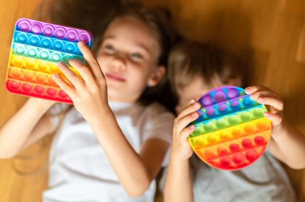 Giocattoli pop sensoriali antistress nelle mani di un bambino. un bambino felice gioca con un semplice giocattolo con fossette a casa.