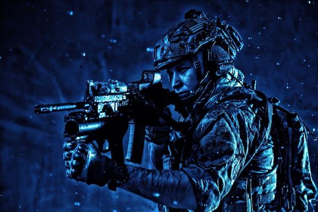 Combattente della squadra antiterrorista, fuciliere delle forze speciali dell'esercito in uniforme da battaglia, auricolare radio tattico, zaino, armatura, fucile di servizio di mira con mirino collimatore, furtivamente nell'oscurità sotto la pioggia