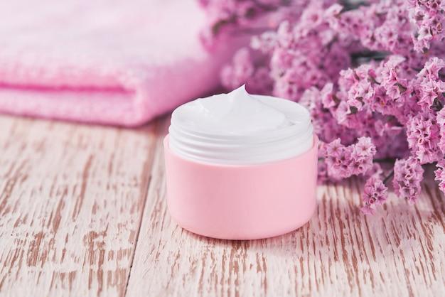 Crema antirughe antietà per la cura del corpo o per la cura del viso igiene idratante lozione con fiori rosa in barattolo di plastica con asciugamano sul tavolo di legno. vasetto di plastica rosa per crema per pelli sensibili.