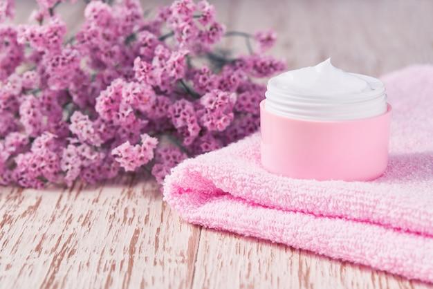 Crema antirughe antietà per la cura del corpo o per la cura del viso igiene idratante lozione con fiori rosa in barattolo di plastica con asciugamano sul tavolo di legno.