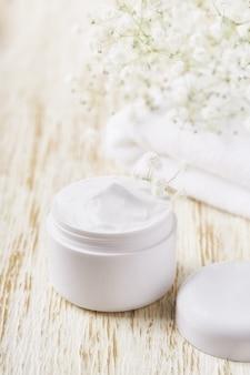 Crema antirughe antietà cura del corpo e cura del viso igiene lozione idratante con fiori bianchi in barattolo di plastica con asciugamano sul tavolo di legno.
