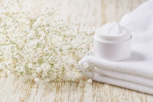 Crema antirughe antietà crema per la cura del corpo e cura del viso igiene idratante lozione con fiori bianchi in barattolo di plastica sul tavolo di legno.