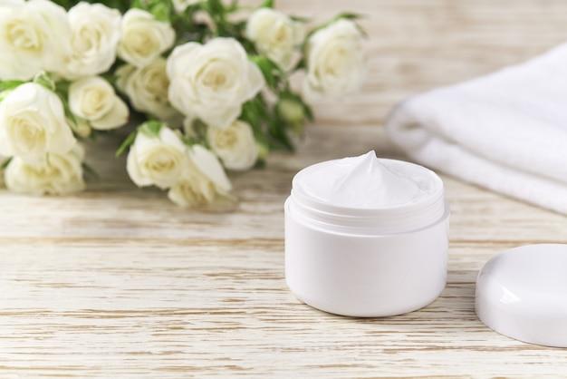 Crema antirughe antietà per pelle sensibile o lozione idratante per l'igiene della cura del viso in barattolo di plastica con asciugamano sul tavolo di legno.