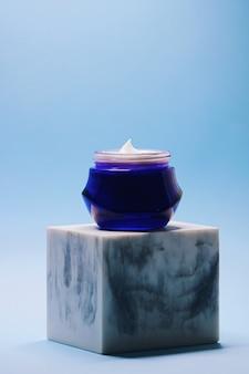 Crema viso antietà per la cura della pelle e dei cosmetici in barattolo su sfondo blu
