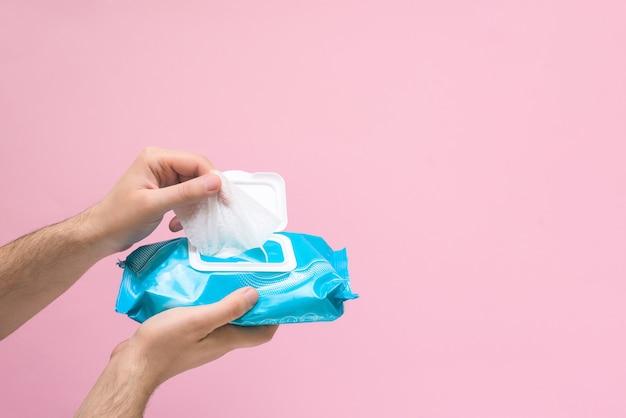Tovagliolo antimicrobico per la disinfezione delle mani durante una pandemia di coronavirus su sfondo rosa. spazio per il testo.