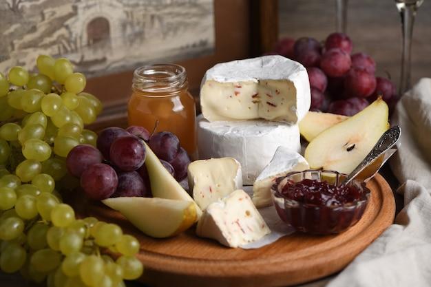 Antipasti. camembert di formaggio con uva, pere a fette e confettura, un ottimo antipasto per il vino.