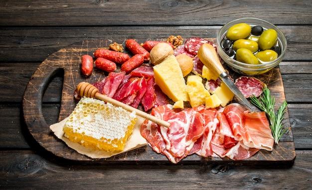 Sfondo di antipasto. assortimento di stuzzichini di carne alla tavola con olive e parmigiano. su uno sfondo di legno.