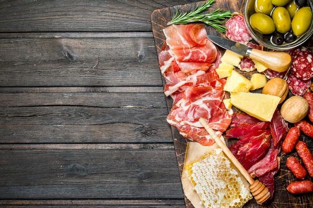 Sfondo di antipasto. assortimento di snack di carne sulla tavola con olive e parmigiano. su uno sfondo di legno.