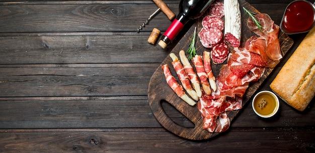 Sfondo di antipasti antipasti di carne italiani con vino rosso. su uno sfondo di legno.