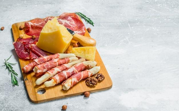 Sfondo di antipasti spuntini di carne e formaggio sulla tavola. su fondo rustico.