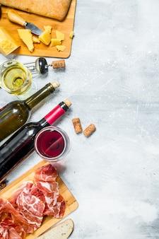 Sfondo di antipasto. vino rosso e bianco con antipasti di carne e formaggi. su fondo rustico.