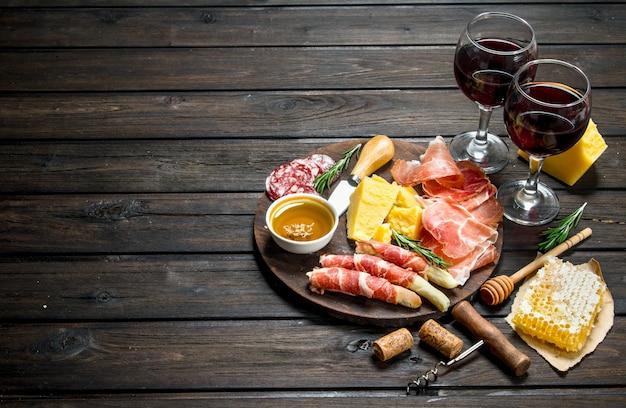 Sfondo di antipasto. vari snack di carne e formaggio con vino rosso. su uno sfondo di legno.