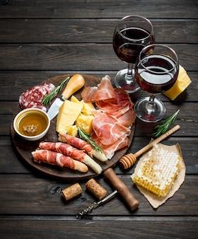 Sfondo di antipasti vari snack di carne e formaggio con vino rosso.