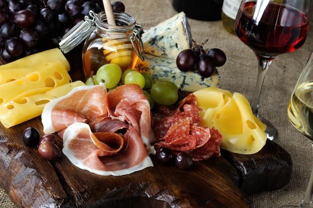 Antipasto piatto di catering con pancetta a scatti, prosciutto, salame, formaggio e uva su uno sfondo di legno