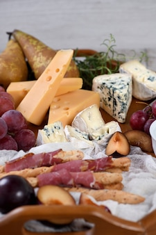 Antipasto. piatto con grissini croccanti avvolti da pancetta essiccata al sole, fette di formaggio brie, camembert, gorgonzola, radamer e moscato con frutta.