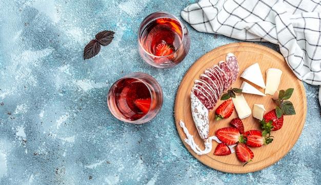 Antipasto spagnolo affettato fuet salame wurst, formaggio camembert, fragole e bicchiere di vino rosato su sfondo blu. banner, posto ricetta menu per testo, vista dall'alto.