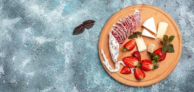 Antipasto spagnolo affettato fuet salame wurst, formaggio camembert, fragole e bicchiere di vino rosato su sfondo blu. formato banner lungo. vista dall'alto.