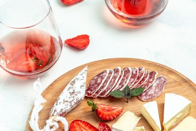 Antipasto spagnolo affettato fuet salame wurst, formaggio camembert, fragole e bicchiere di vino rosato su sfondo bianco. sfondo di ricetta alimentare. avvicinamento.