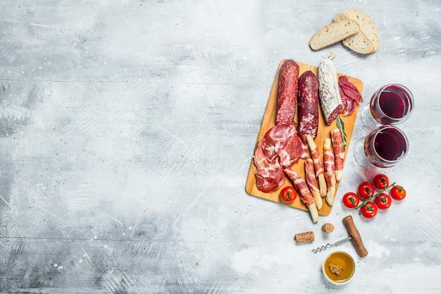 Superficie antipasto. diversi spuntini italiani con vino rosso. su una superficie rustica.