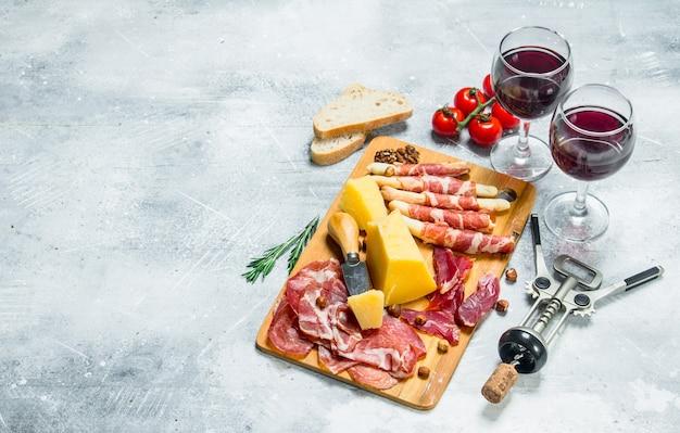 Superficie antipasto. vari snack di carne e formaggio con vino rosso. su una superficie rustica.