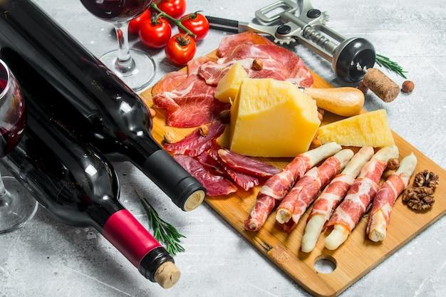 Antipasto. vari snack di carne e formaggio con vino rosso. su un rustico.