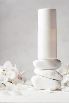 Deodorante roll-on antitraspirante su pila di ciottoli bianchi su superficie di intonaco chiaro con fiori di mela. copia spazio