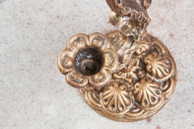 Candeliere d'ottone antico per una candela su fondo concreto. copia spazio per il testo.