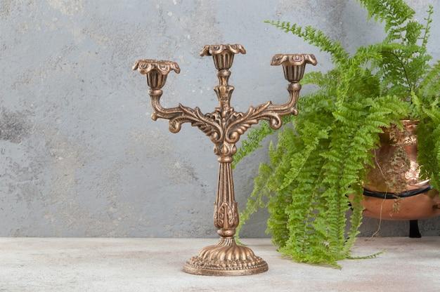 Candeliere d'ottone antico per tre candele su fondo concreto. copia spazio per il testo.