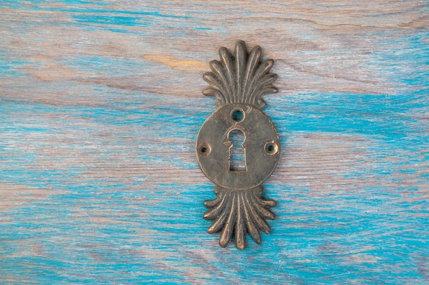 Coperchio della serratura del buco della serratura in ottone antico su fondo di legno blu. copia spazio per il testo.