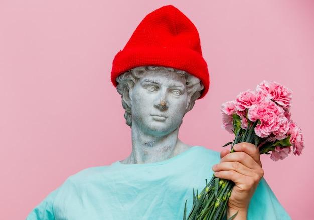 Busto antico del maschio in cappello con bouquet di garofani