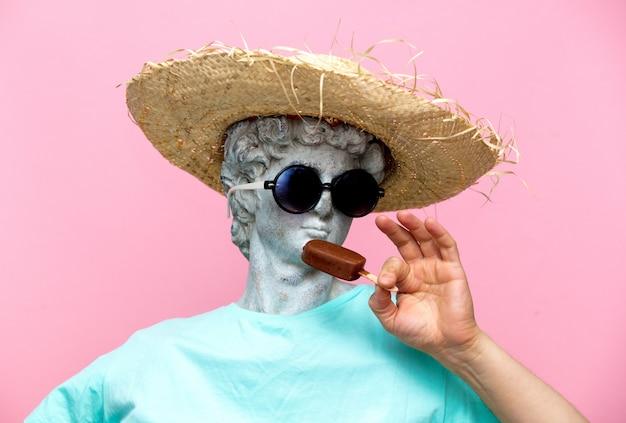 Busto antico del maschio in cappello con gelato su sfondo rosa.