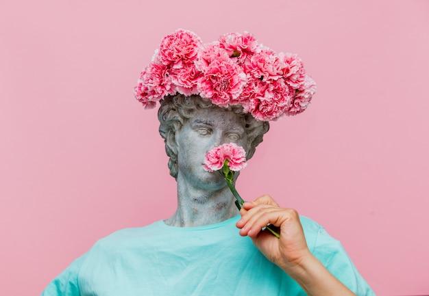 Busto antico del maschio con bouquet di garofani in un cappello