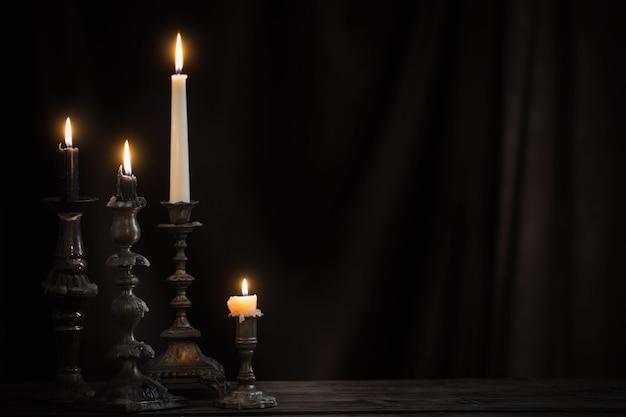 Candeliere antico con candela accesa sul vecchio tavolo in legno su sfondo tenda di velluto nero